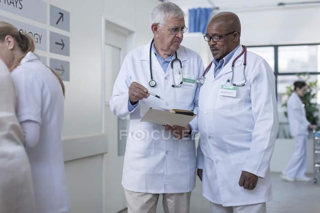 Dos médicos en pasillo de hospital hablar de archivo - foto de stock