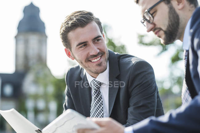 Two young businessmen sitting on bench, discussing files — Stock Photo