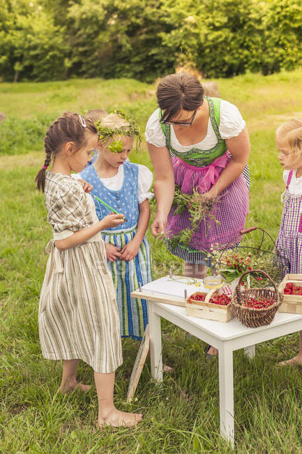 Three little girls and their educator in traditional clothes on meadow — Stock Photo