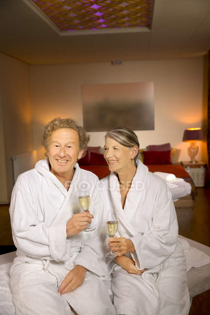 Smiling senior couple in bathrobes holding champagne glasses — Stock Photo