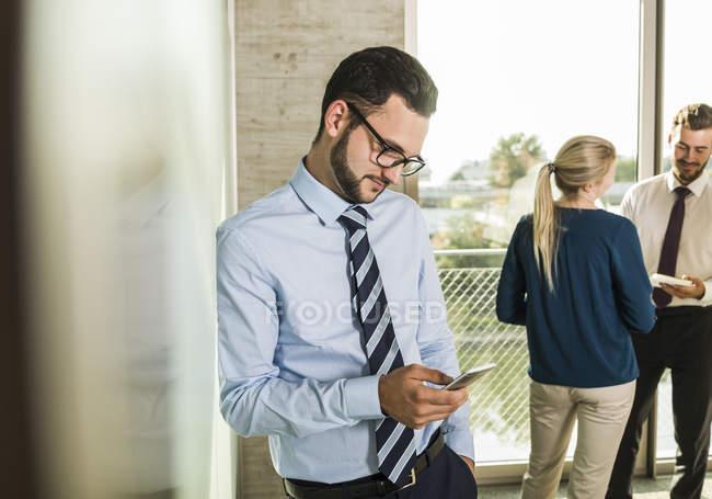 Homem de negócios usando smartphone com colegas no fundo — Fotografia de Stock