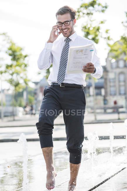 Jeune homme d'affaires debout dans la fontaine, parlant au téléphone — Photo de stock