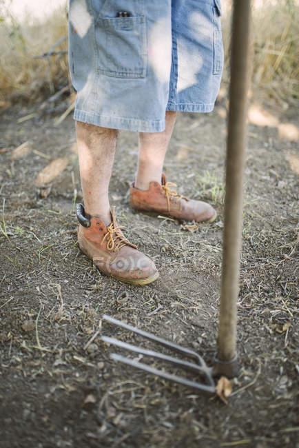 Pernas de um fazendeiro além de machado — Fotografia de Stock