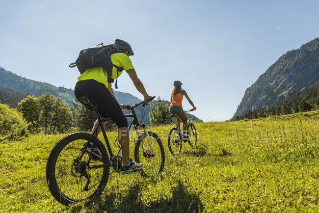 Австрия, Тироль, Таннинская долина, молодая пара на горных велосипедах в пейзаже — стоковое фото