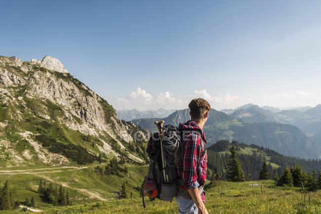 Austria, Tyrol, Tannheimer Tal, young man hiking on alpine meadow — Stock Photo
