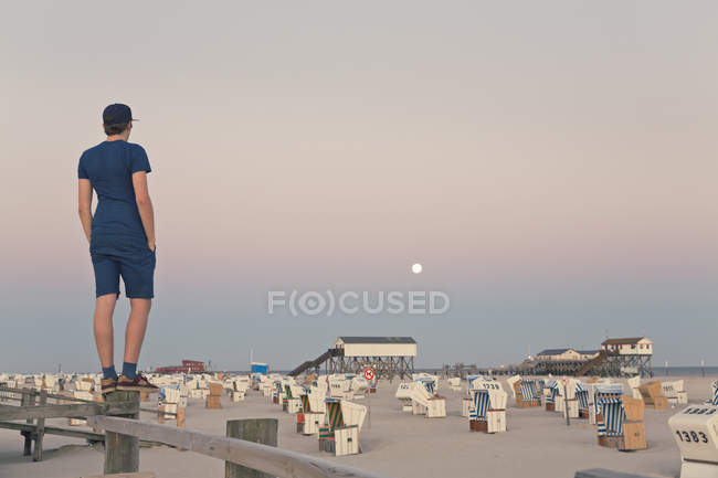 Germany, St Peter-Ording, young man standing on wooden fence looking at the beach — Stock Photo