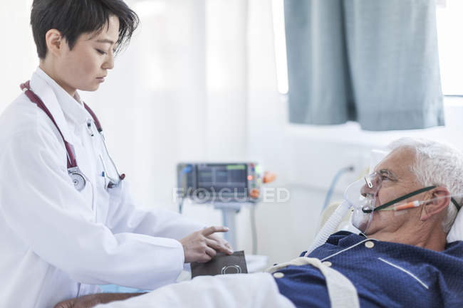 Doctor taking blood pressure of senior man with oxygen mask in a hospital — Stock Photo