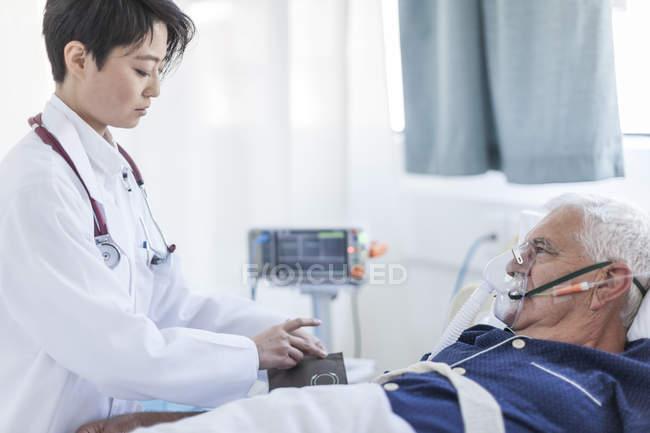 Médico tomando la presión arterial de senior hombre con máscara de oxígeno en un hospital - foto de stock