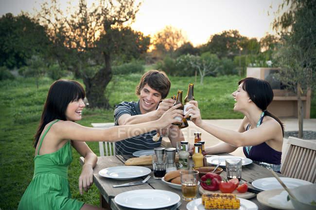 Heureux amis assis à la table du jardin sur un barbecue clinquant bouteilles de bière — Photo de stock
