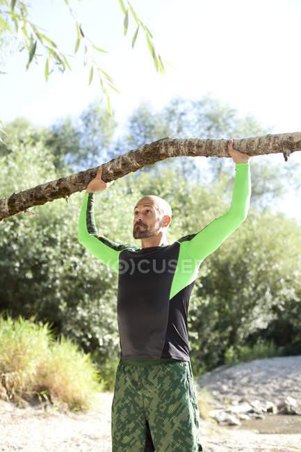Homem fazendo exercício CrossFit com tronco de árvore — Fotografia de Stock