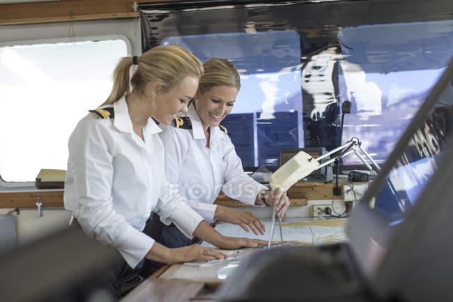 Deux officiers de pont femmes travaillant sur une carte nautique — Photo de stock