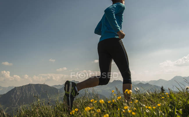 Austria, Tyrol, Tannheim Valley, young man jogging in mountains — Stock Photo