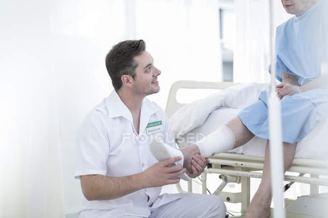 Krankenschwester, die Fürsorge für ältere Patienten im Krankenhausbett — Stockfoto