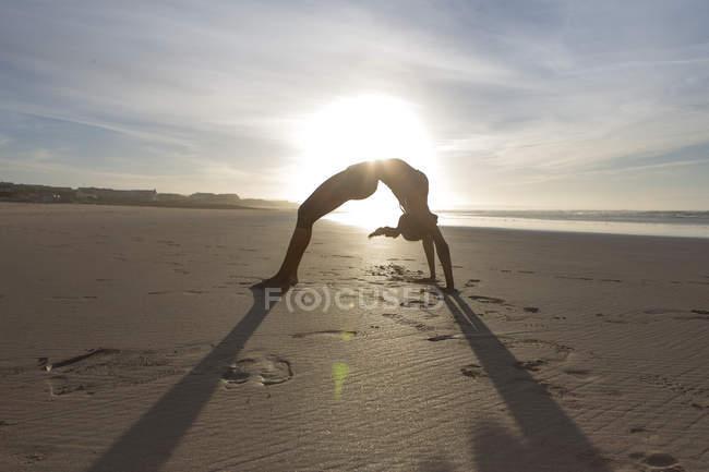 Силует молоду жінку в міст розташування на пляжі в підсвічування — стокове фото