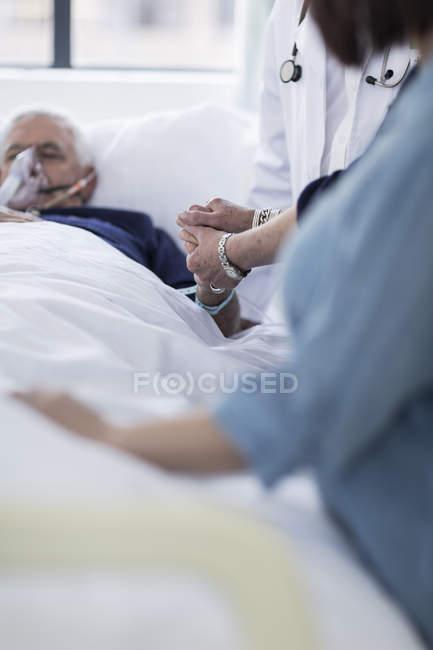 Больное посещение постели пожилого человека в больнице — стоковое фото