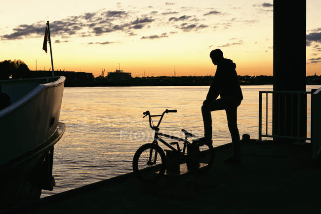 Silueta de Alemania, Hamburgo, de un hombre joven con moto en un embarcadero en la luz del atardecer - foto de stock