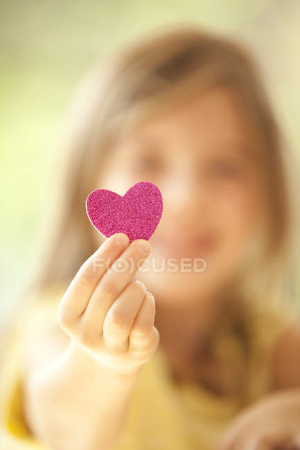 Close-up of girl holding glittering heart — Stock Photo