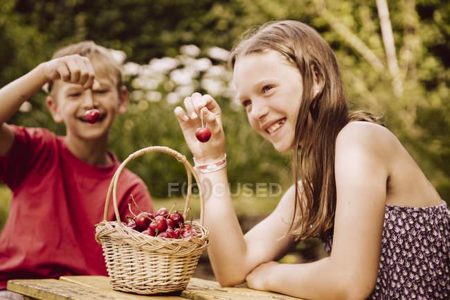 Girl and boy enjoying cherries in garden — Stock Photo