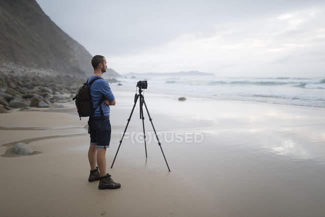 Spain, Valdovino, photographer standing on the beach taking photos with a tripod — Stock Photo