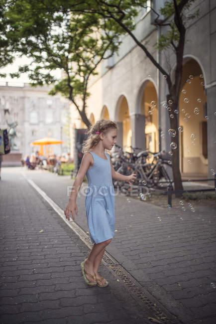 Niña usando ligh vestido de verano azul viendo burbujas de jabón - foto de stock