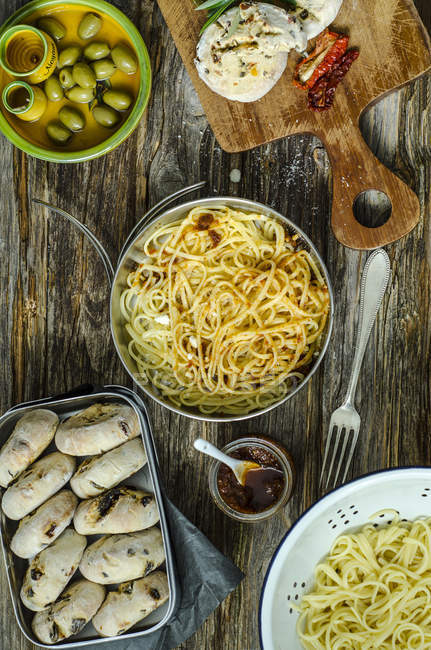 Spaghetti with tomato pesto, parmesan and selfmade buns of olives and tomatoes on a wooden board — Stock Photo