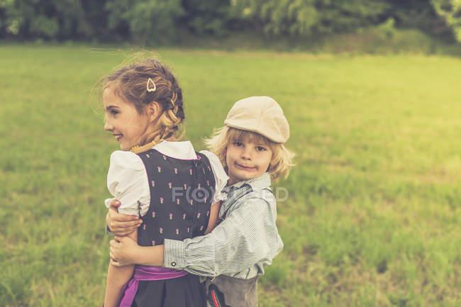 Little boy hugging girl on a meadow — Stock Photo