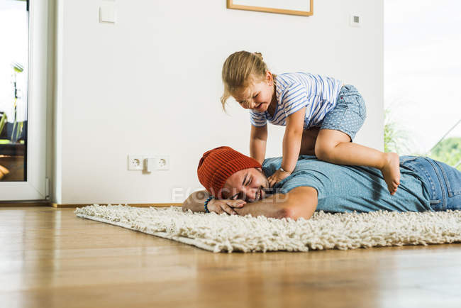Daughter kneeling on father's back lying on floor — Stock Photo
