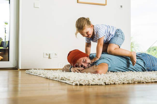 Tochter auf Vaters Rücken am Boden liegend kniend — Stockfoto