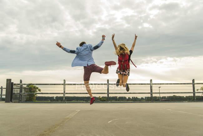 Couple jeune enthousiaste, sauter sur le niveau de stationnement — Photo de stock