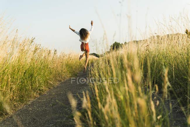 Mulher jovem entusiasta saltando no caminho no campo — Fotografia de Stock