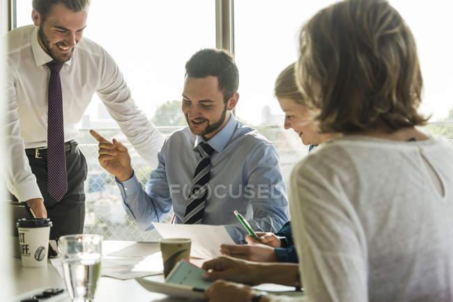 Des hommes d'affaires souriants se réunissent en salle de conférence — Photo de stock