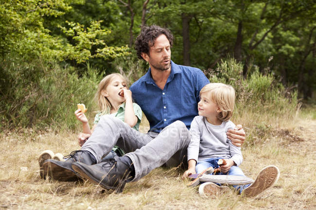 Padre con dos hijos teniendo una comida campestre en el borde del bosque - foto de stock