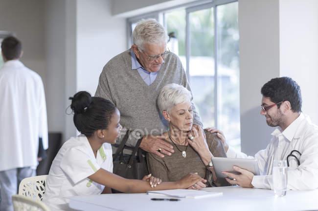 Seniorenpaar in Klinik im Gespräch mit Arzt und Krankenschwester — Stockfoto