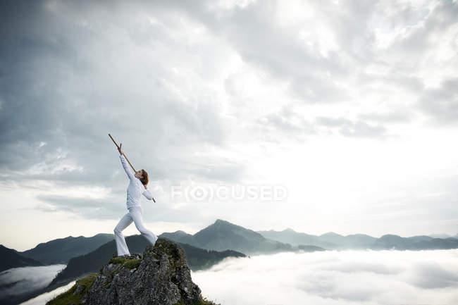 Австрия, Кранцхорн, Взрослая женщина, упражняющаяся с боевой палкой на вершине горы — стоковое фото
