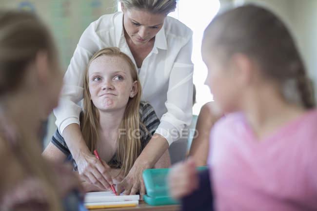 Insegnante correggere brutto test di scolara in classe — Foto stock