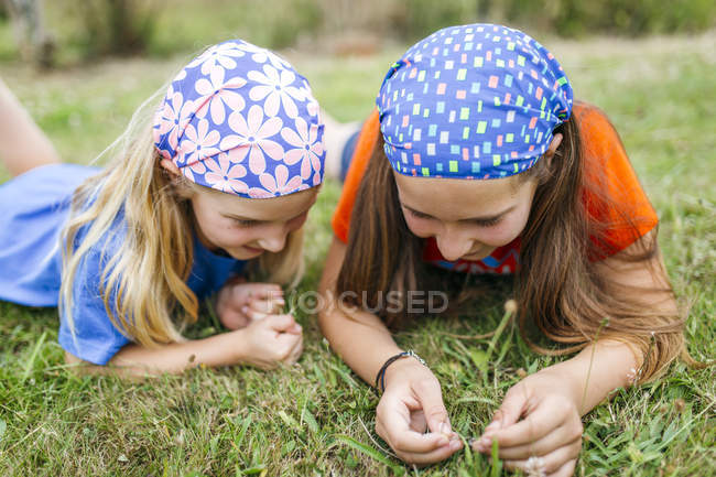 Elementary age sisters in headscarves lying on meadow and examining grass — Stock Photo