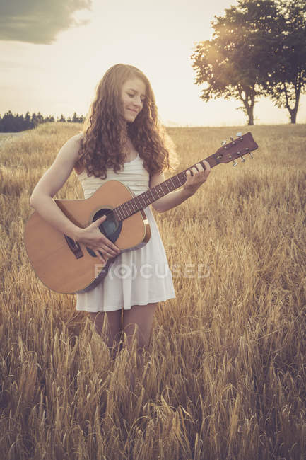 Frau spielt Gitarre im Feld — Stockfoto