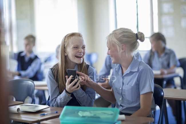 Due studentesse sorridenti in classe a guardare il cellulare — Foto stock