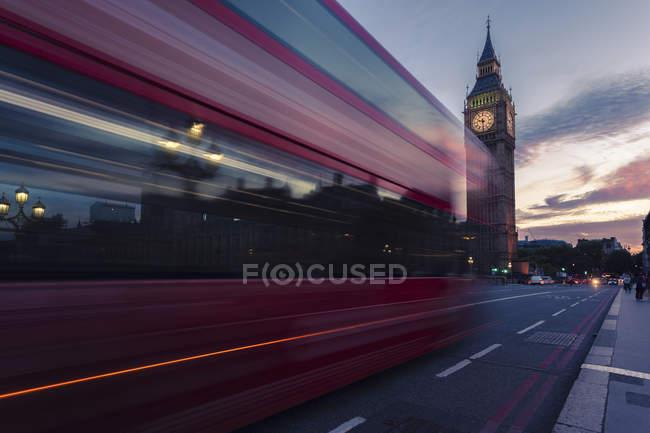 Reino Unido, Londres, autobús rojo pasando Westminster Bridge con la torre Big Ben en el fondo al atardecer - foto de stock