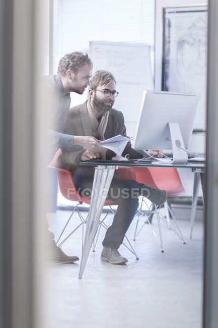 Zwei Männer arbeiten im Büro gemeinsam an einem Computer — Stockfoto