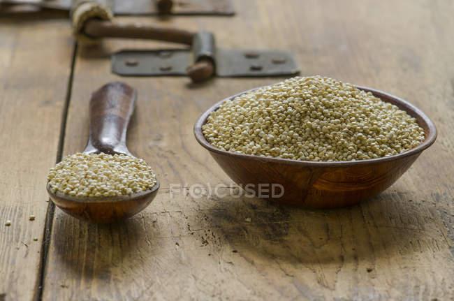 Ciotola di legno e cucchiaio di quinoa su legno — Foto stock