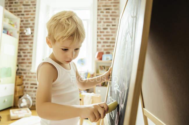 Маленький хлопчик, спираючись на крейда ради в кімнаті — стокове фото