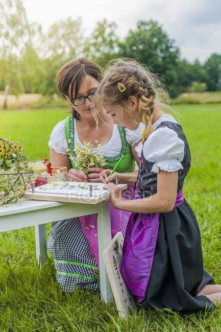 Young girl wearing dirndl learning to draw plants — Stock Photo