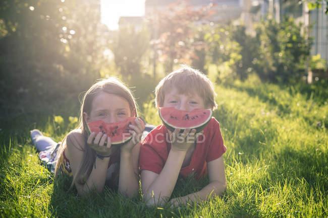 Menino e menina deitados em um prado e segurando fatias de melancia — Fotografia de Stock
