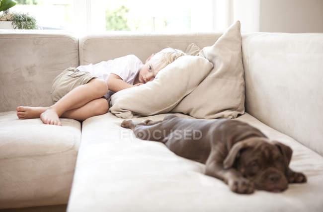 Грустный мальчик лежит на диване в гостиной — стоковое фото