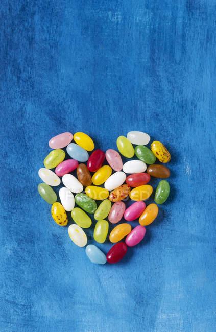Jellybeans in heart shape, blue wood — Stock Photo