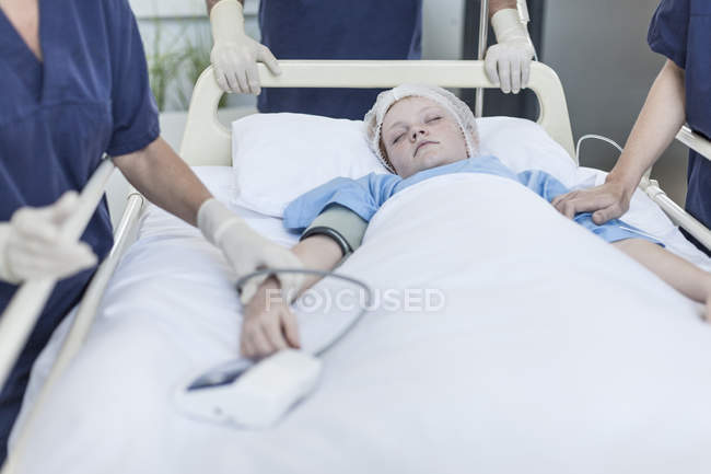 Girl lying in hospital bed with surgeons around — Stock Photo