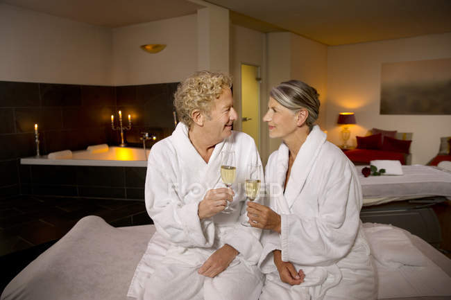 eef5a6ebd2 Smiling senior couple in bathrobes clinking champagne glasses — Stock Photo