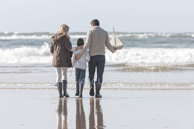 Family walking on beach with toy boat — Stock Photo