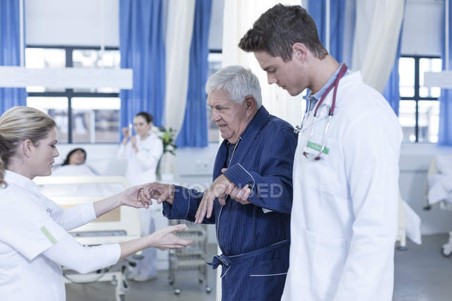 Hospital staff supporting senior patient — Stock Photo
